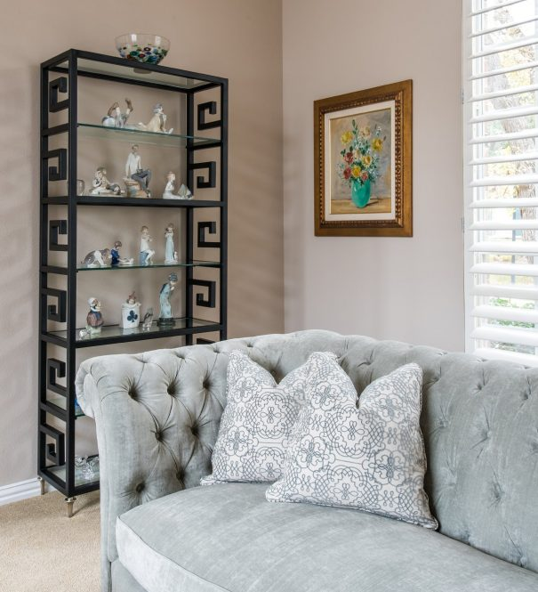 tufted couch and bookshelf